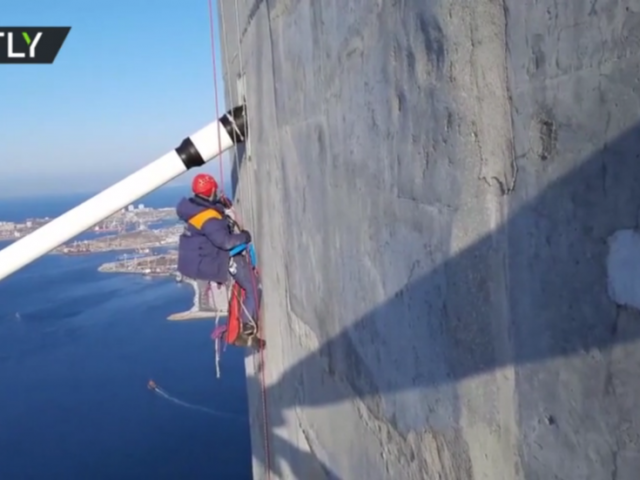 Watch as daring alpinist cleans 320m-high Russky Bridge after freak storm glazes it with ice (VIDEO)